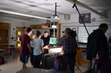 """Xploration Earth 2050"" host Chuck Pell interviews students about the augmented reality sandbox in teacher Tom Lavanga's classroom."