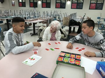 Students spend quality time with a senior citizen chatting and playing Apples-to-Apples.