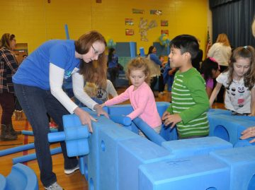 Morgan Stanley Documentation Manager Aideen Connolly (left) assists Conshohocken Elementary School students with pieces of the Imagination Playground.